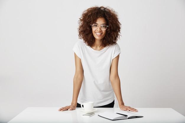 Signora africana di affari che sorride nell'ufficio. muro bianco.
