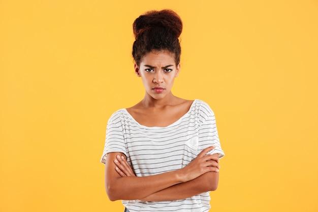 Signora africana dispiaciuta arrabbiata che si tiene per mano piegata isolata