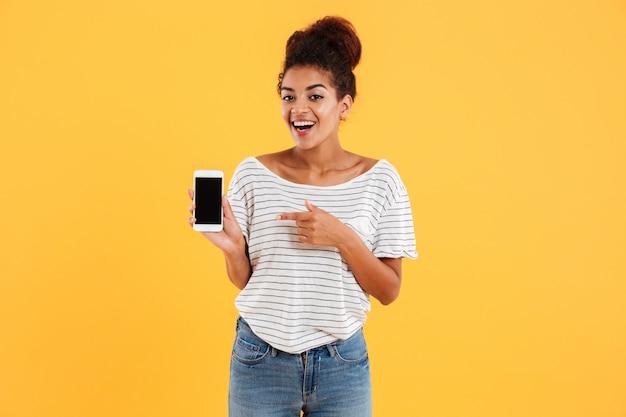 Signora africana felice che mostra telefono con lo schermo in bianco isolato