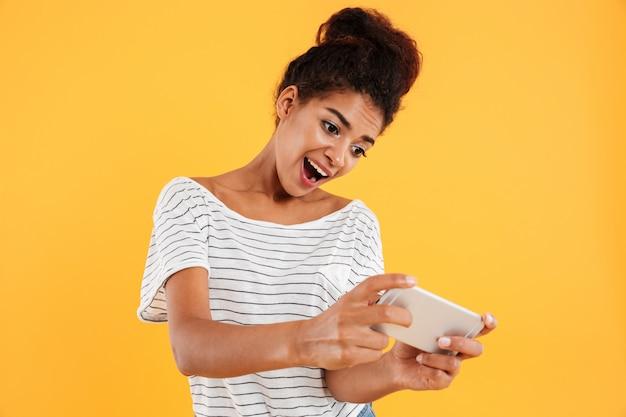 Signora africana positiva divertente che gioca gioco sul telefono isolato