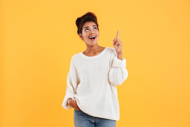 Signora afroamericana felice che indica con il dito fino a copiare spazio