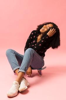 Signora afroamericana felice che si siede sullo skateboard