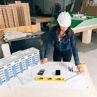 Signora afroamericana in casco di sicurezza che sta vicino al modello di costruzione