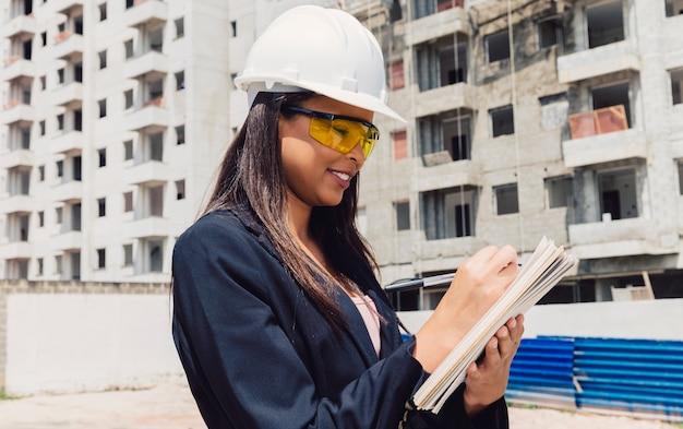 Signora afroamericana in casco di sicurezza con il blocchetto per appunti vicino alla costruzione in costruzione