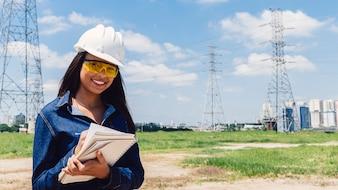 Signora afroamericana sorridente in casco di sicurezza che cattura le note vicino alla linea ad alta tensione