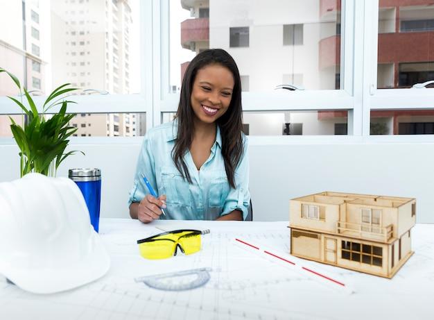 Signora afroamericana sorridente sulla sedia con la penna vicino al casco di sicurezza e modello di casa sul tavolo