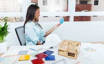 Signora afroamericana sorridente sulla sedia vicino al piano e modello di casa sul tavolo
