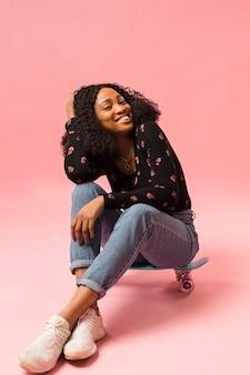 Signora afroamericana sveglia che si siede sullo skateboard
