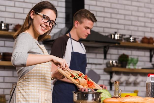 Signora allegra che cucina insalata vicino al ragazzo