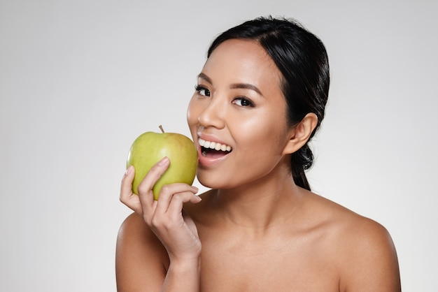 Signora allegra che sorride e che mangia mela verde