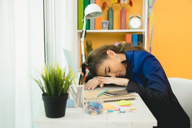 Signora allegra di affari che lavora al computer portatile in ufficio