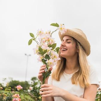 Signora allegra in cappello con fioriture bianche