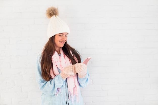 Signora allegra in guanti, bobble cappello e sciarpa con smartphone