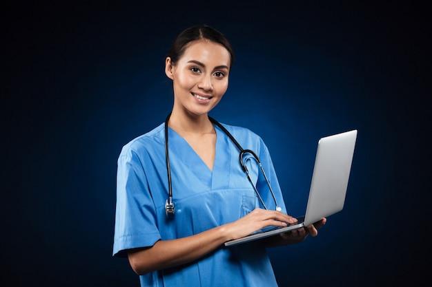 Signora allegra in uniforme medica facendo uso del computer portatile