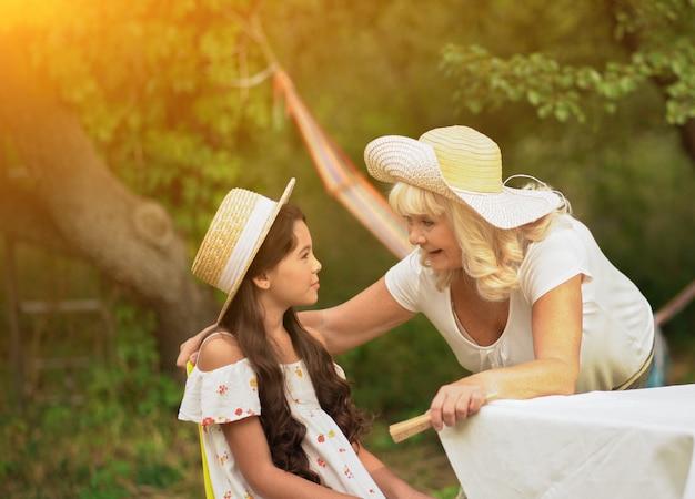 Signora anziana che parla con sua nipote nel parco