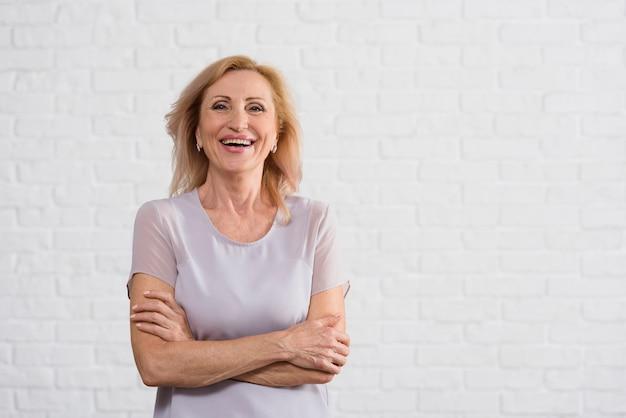 Signora anziana di smiley che esamina macchina fotografica con la priorità bassa del mattone