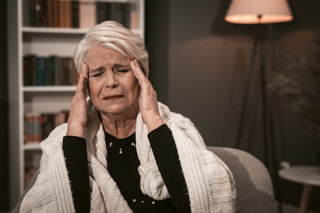 Signora anziana si massaggia le tempie con le mani