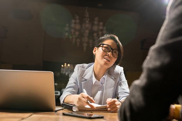 Signora asiatica che lavora con il collega in ufficio scuro