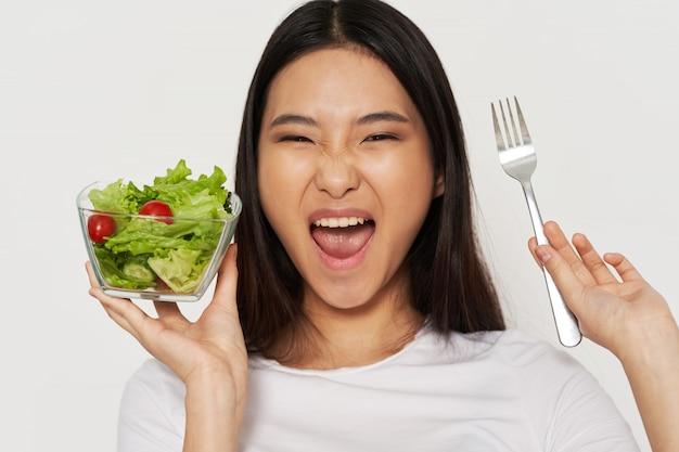 Signora asiatica che mangia un'insalata