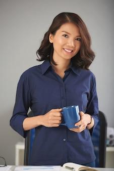 Signora asiatica che propone con la tazza