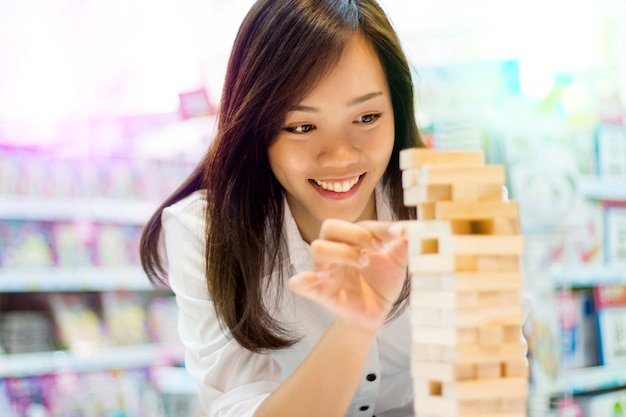 Signora asiatica gioca a jenga