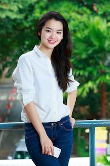 Signora asiatica in abiti casual utilizzando un telefono cellulare