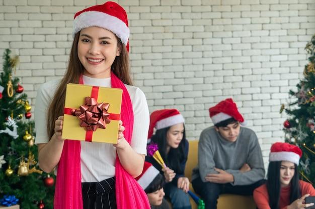 Signora asiatica in un bel vestito con una confezione regalo. carino sorridente. divertirsi festa di natale. vigilia di natale,