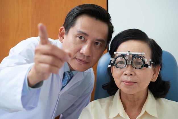 Signora asiatica senior che indossa la struttura e l'oftalmologo della lente di prova che indicano durante il controllo di vista