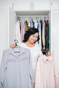 Signora asiatica senior che sta davanti al guardaroba aperto a casa e che tiene le bluse sui ganci