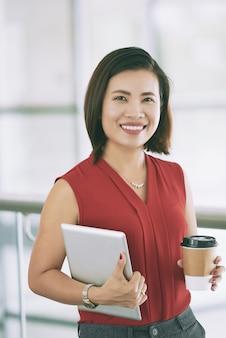 Signora asiatica sicura di affari che posa all'interno sul balcone con caffè e la compressa asportabili