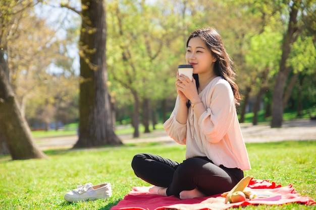 Signora asiatica sorridente che beve caffè e che si siede sul prato inglese
