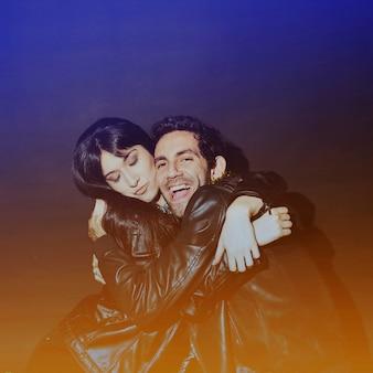 Signora attraente che abbraccia il ragazzo ridendo in giacche di pelle