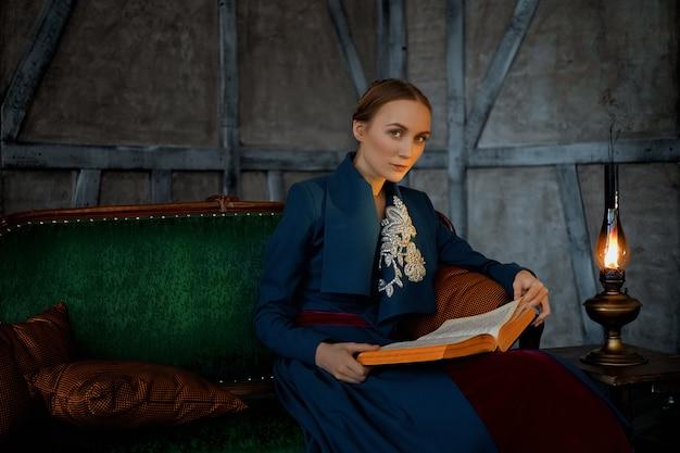Signora attraente che legge libro antico vicino alla lampada di cherosene d'annata