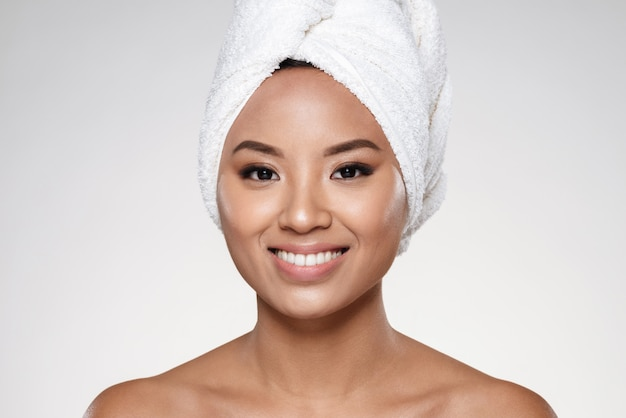 Signora attraente senza trucco con un asciugamano sulla testa che sorride alla macchina fotografica