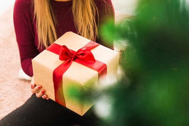 Signora bionda con scatola regalo sul tappeto