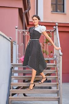 Signora carina e alla moda in abito lungo a strisce che scende le scale