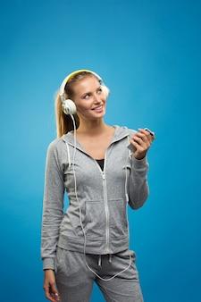 Signora caucasica di bella misura bionda nello sport grigio con musica d'ascolto delle cuffie. isolato sulla parete blu