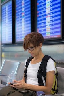Signora che aspetta nel terminale di aeroporto facendo uso del telefono