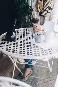 Signora che beve il suo bicchiere di vino rosso in un negozio di vini