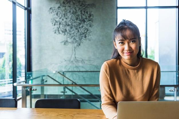 Signora che lavora al computer portatile al tavolo