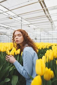 Signora che osserva via vicino ai fiori