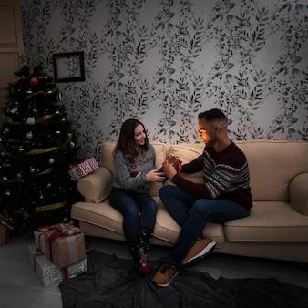 Signora che presenta il pacchetto regalo al ragazzo sul divano vicino all'albero di natale