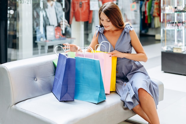 Signora che si siede sullo strato che osserva in suoi sacchetti di acquisto