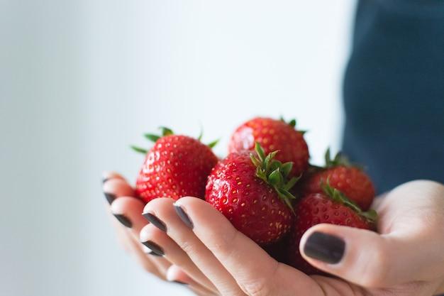 Signora che tiene fresche fragole mature nelle sue mani