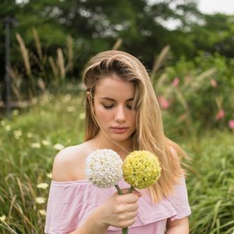 Signora che tiene i fiori luminosi nel parco