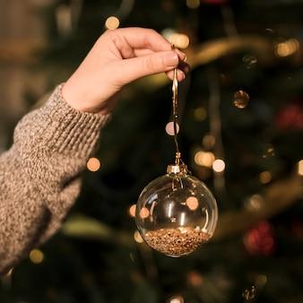 Signora che tiene ornamento trasparente palla di natale