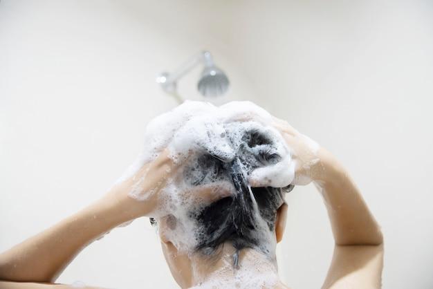 Signora che usa shampoo lavarsi / pulirsi i capelli in un bagno con spruzzi d'acqua