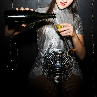 Signora che versa champagne in vetro vicino alla palla da discoteca