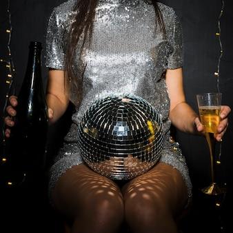 Signora con bottiglia di champagne, vetro e palla da discoteca