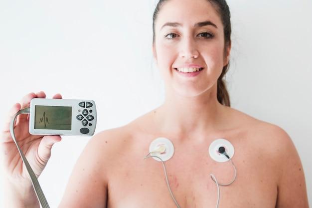 Signora con elettrodi tenendo monitor con cardiogramma